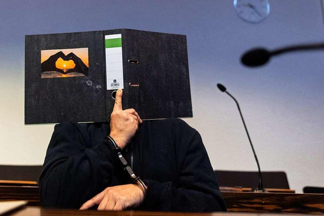 Aktenordner vor dem Kopf, Ketten an den Händen: Der Angeklagte Bernhard H.  | Foto: Patrick Seeger (dpa)