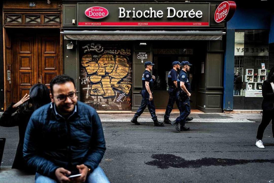 Polizisten laufen einen Tag nach der E...iale von Brioche Dorée in Lyon vorbei.  | Foto: JEFF PACHOUD (AFP)