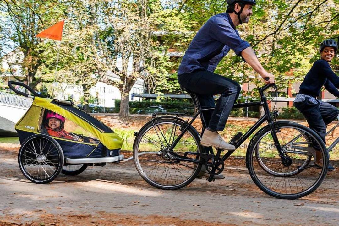 Im Gespann unterwegs: Die Hülle des An...s schützt das Kind vor Wind und Regen.  | Foto: www.croozer.de (dpa)