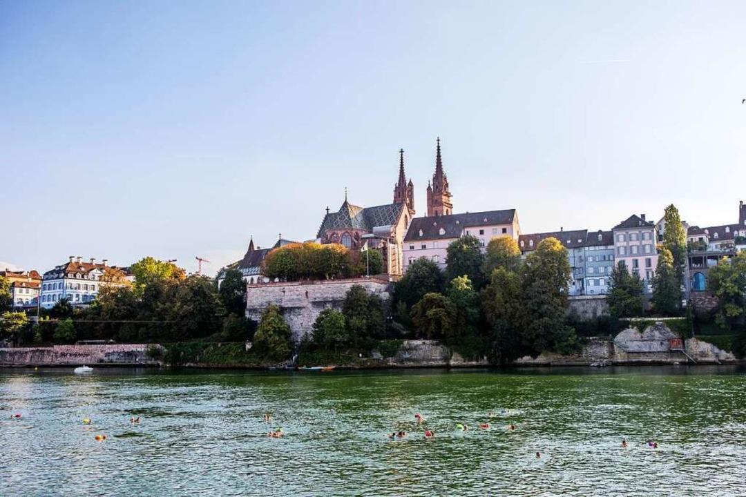 Im Hintergrund das Basler Münster &#82...nsieht, sieht die Schwimmer im Rhein.   | Foto: JOSS ANDRES