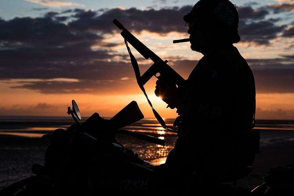 Silhouette eines Mannes in Uniform und auf historischem Motorrad am Strand von Arsnelles. (Foto: JOEL SAGET (AFP))