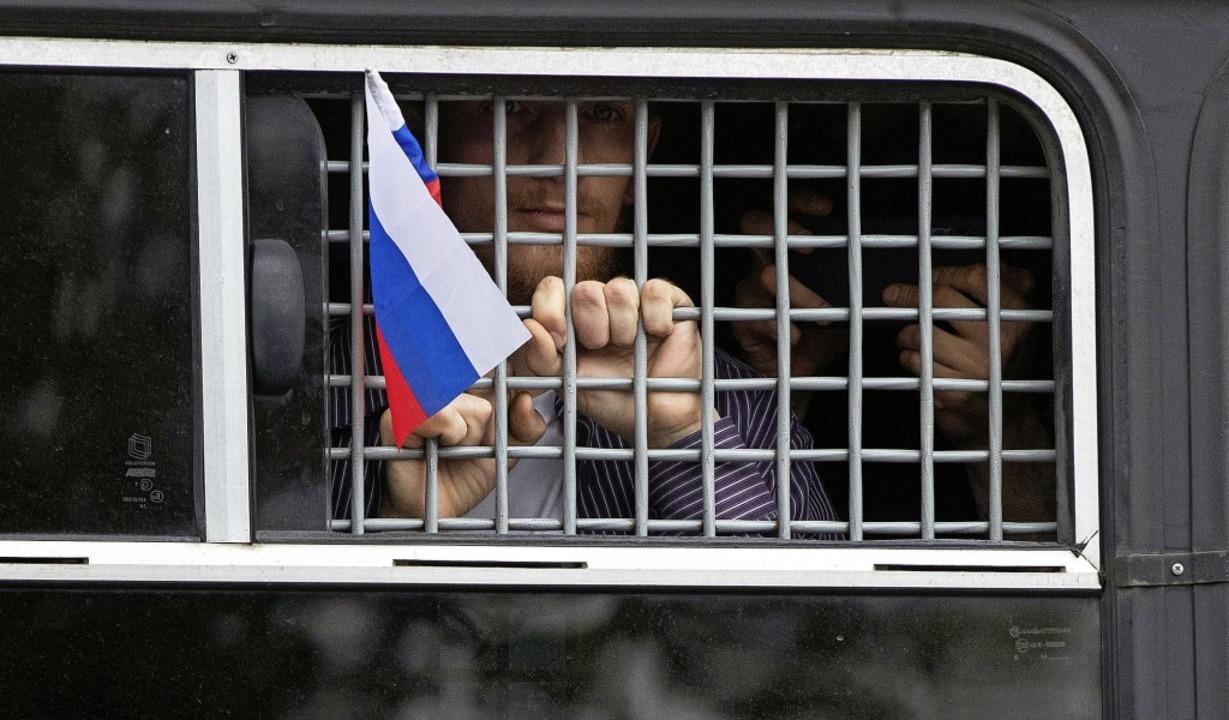 Ein verhafteter   Demonstrant schwenkt...izeiauto heraus eine russische Fahne.   | Foto: Pavel Golovkin (dpa)