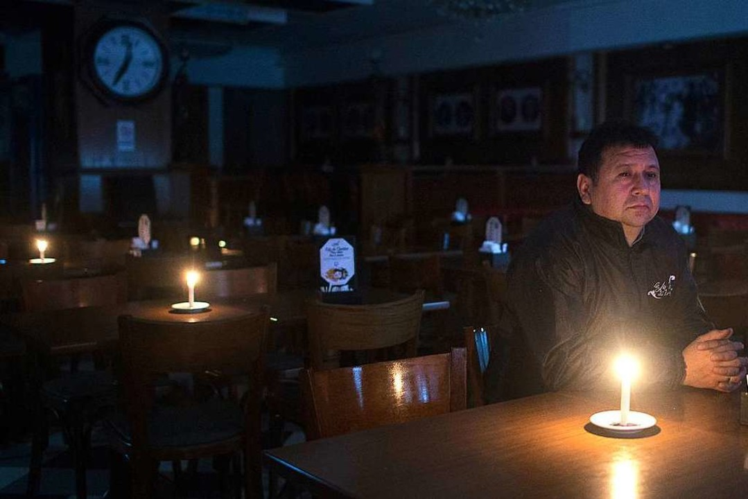 Kerzenschein: Ein Mann sitzt im Dunkeln in einer Bar in Buenos Aires.  | Foto: Mario De Fina (dpa)