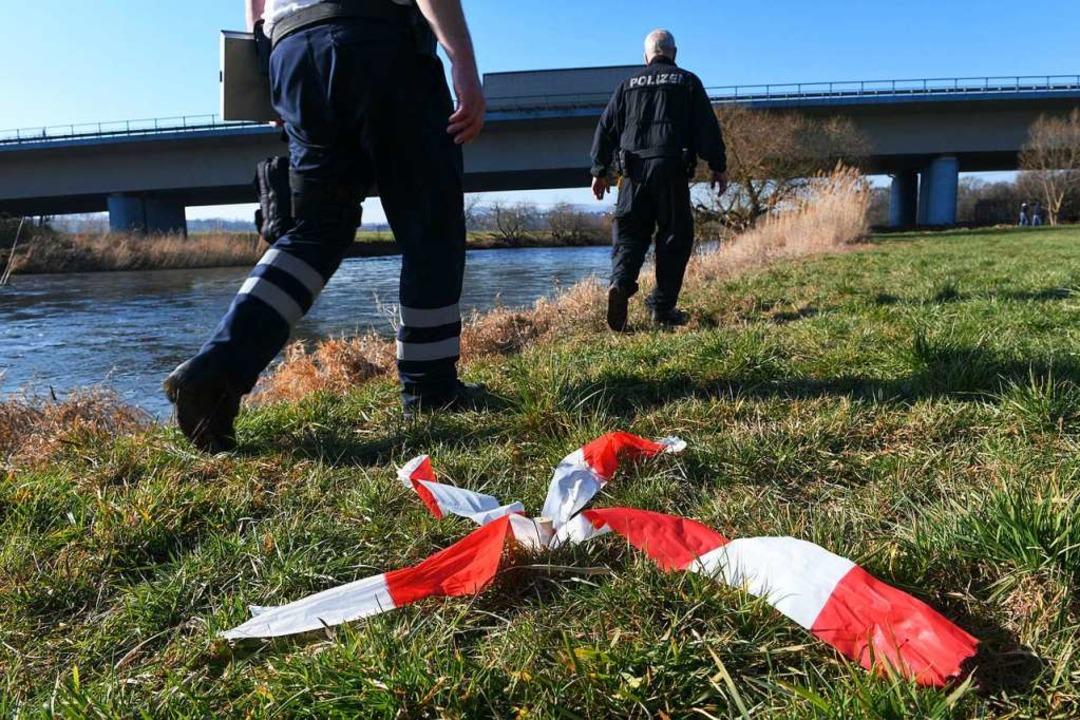 Polizeikräfte gehen am Ufer der Fulda ... in dem Fluss die Leiche eines Kindes.  | Foto: Uwe Zucchi (dpa)