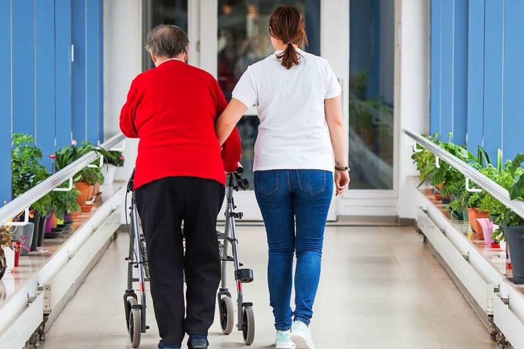 Eine Pflegerin führt eine ältere Frau ...in einem Seniorenzentrum (Symbolbild).    Foto: Christophe Gateau