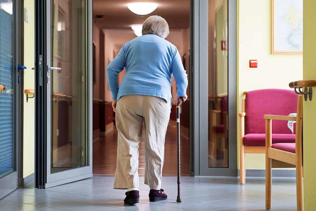 Eine Frau geht in einem Pflegeheim an einem Gehstock  | Foto: Sebastian Kahnert (dpa)