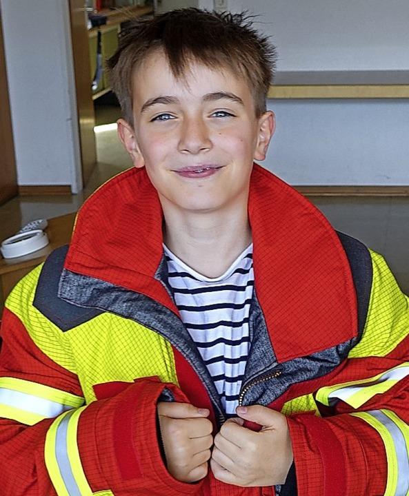 Maximilian probiert eine Feuerwehrjacke an.   | Foto: privat