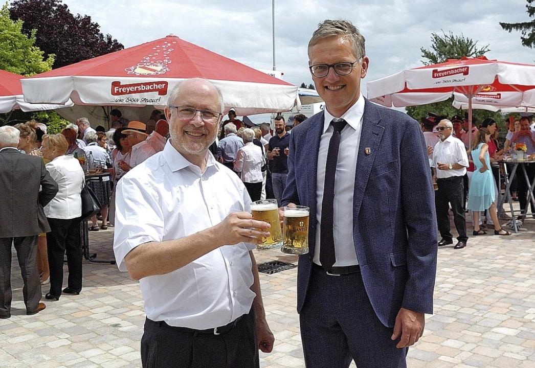 Pfarrer Bernhard Schneider (links) und...r stoßen auf den neuen Kirchplatz an.   | Foto: Jürgen Schweizer