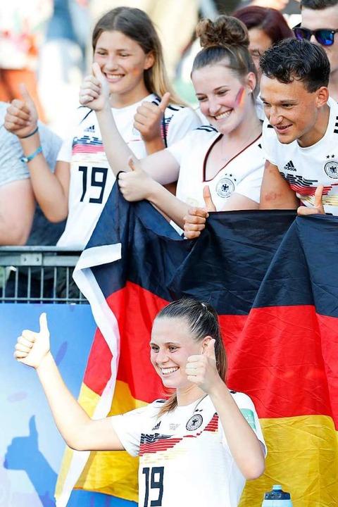 Die Freiburgerin  Klara Bühl präsentie...sspfiff zusammen mit deutschen  Fans.   | Foto: Ding Xu (dpa)