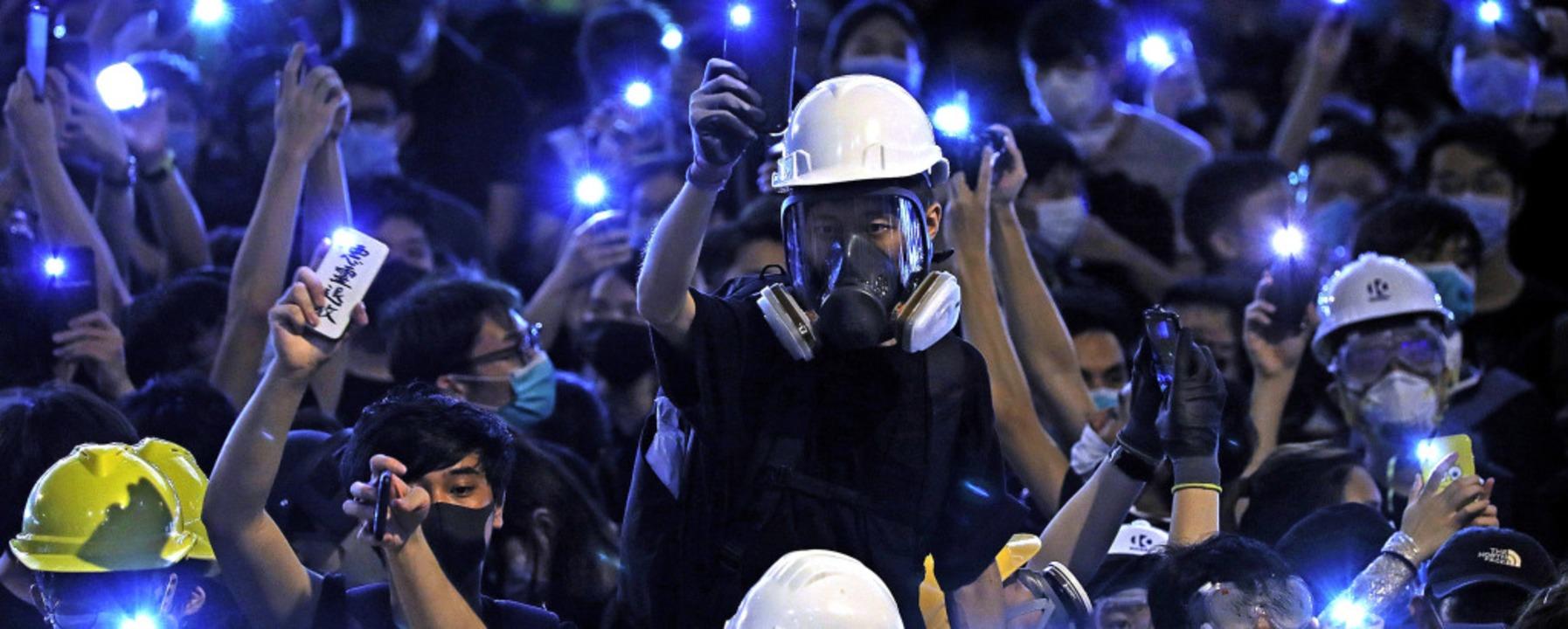 Mit Handyleuchten gegen das politische...ausende junge Menschen auf die Straße.  | Foto: Vincent Yu (dpa)
