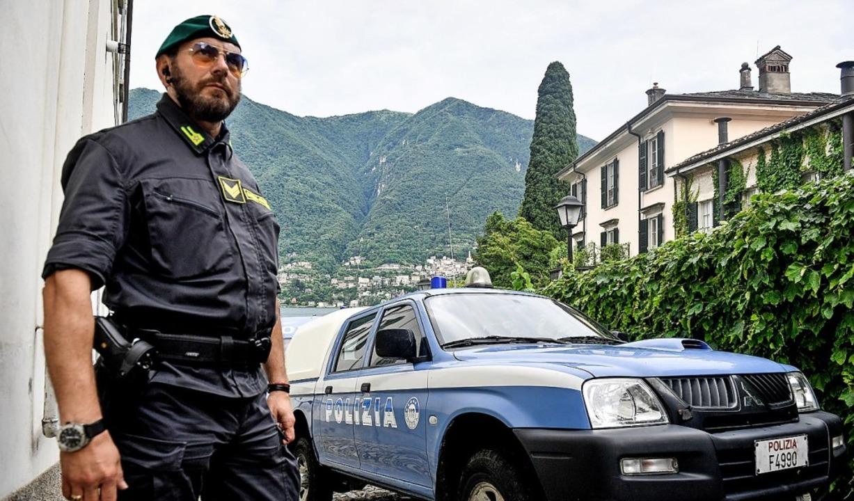 Ein Polizist steht zur Sicherheit vor ...woodstar George Clooney am Comer See.   | Foto: Claudio Furlan (dpa)