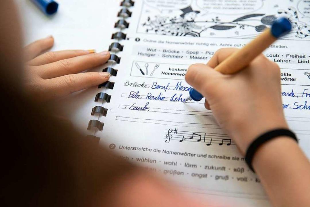 Schulbetreuer helfen auch bei den Hausaufgaben (Symbolbild).  | Foto: Florian Schuh (dpa)