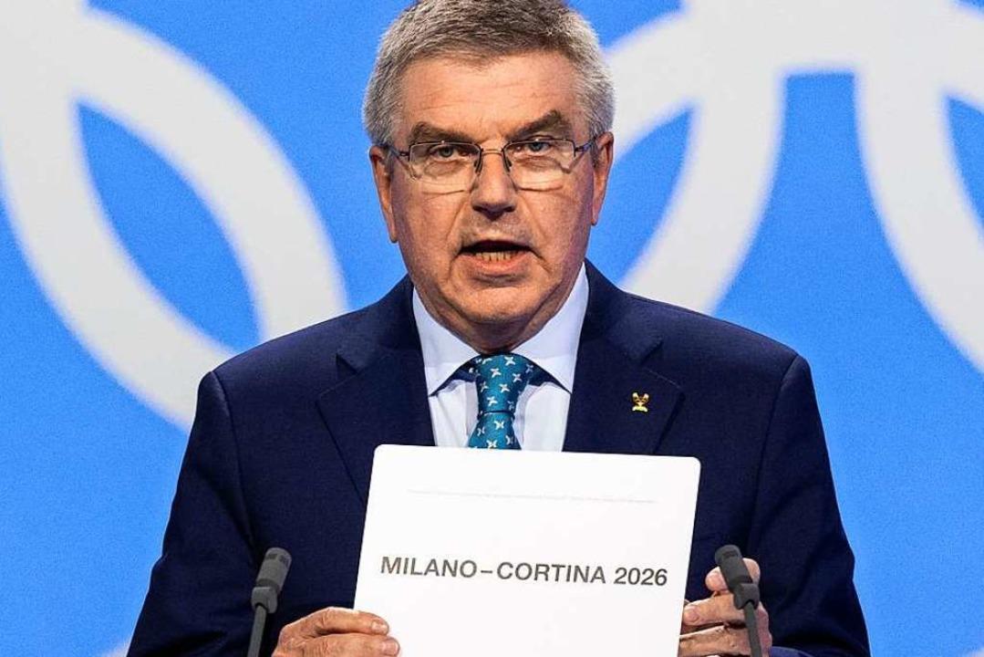 IOC-Präsident Thomas Bach zeigt den Si...richter der Winterspiele 2026: Mailand  | Foto: Laurent Gillieron (dpa)