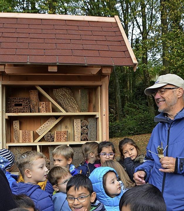 Manfred Ehrler zeigt Kindern das Insektenhotel im Stadtgarten.  | Foto: Gerhard Walser