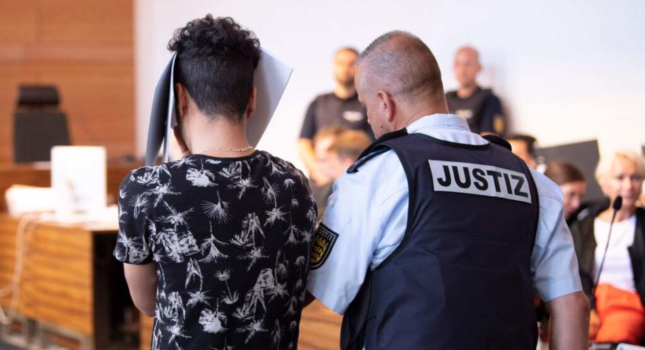 Einer der Angeklagten wird in den Gerichtssaal geführt.  | Foto: THOMAS KIENZLE (AFP)