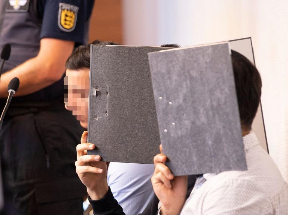 Einige Angeklagte verdecken ihr Gesicht vor den Kameras.  | Foto: THOMAS KIENZLE (AFP)