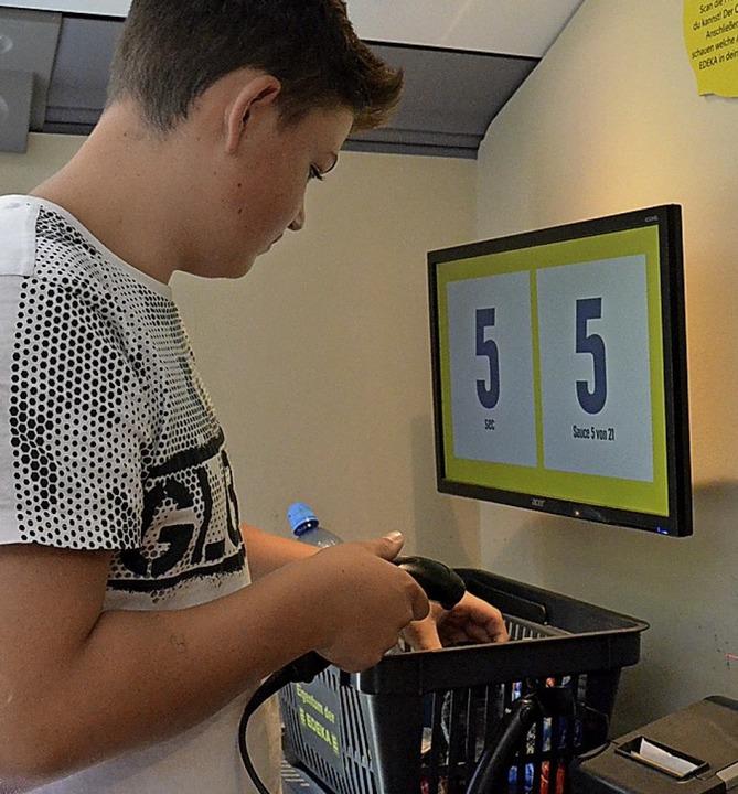 Waren schnell scannen: Ein Schüler ver...an einer der Aufgaben im Frischemobil.    Foto: Sebastian Barthmes