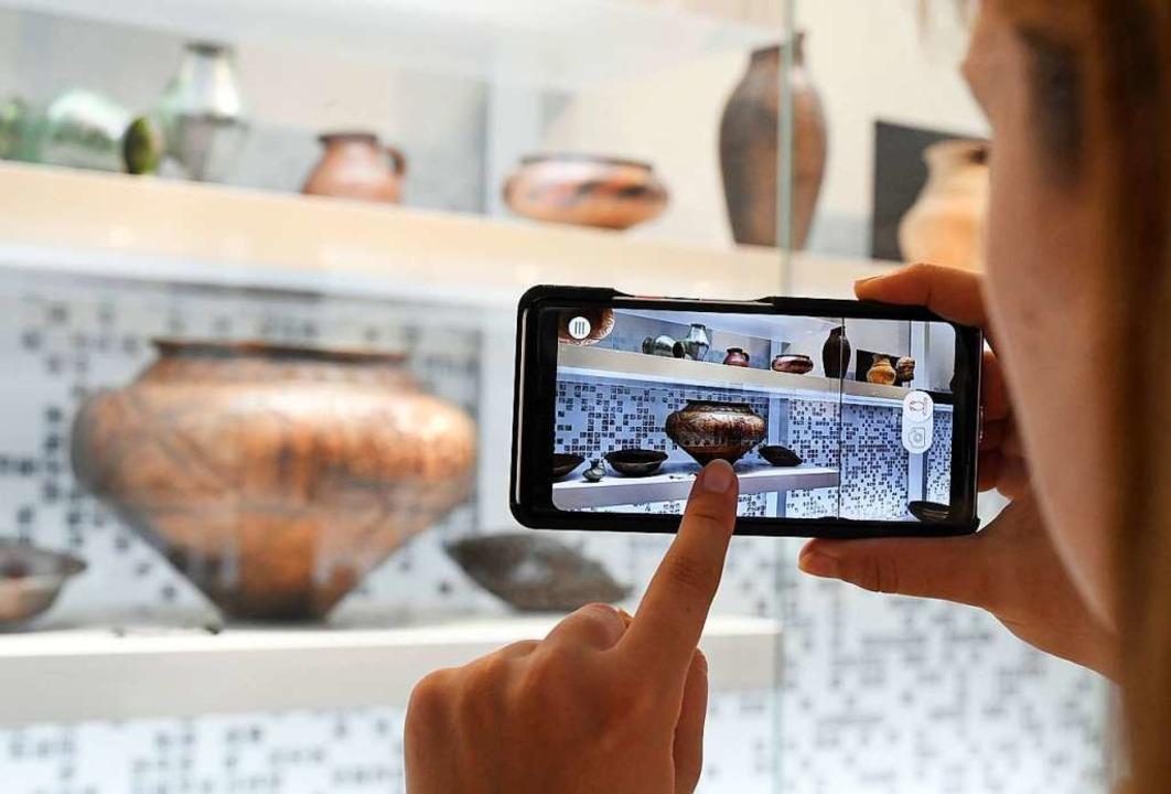 Mithilfe eines Expophones recherchiert... Besucherin über ein bestimmtes Objekt  | Foto: Uli Deck (dpa)