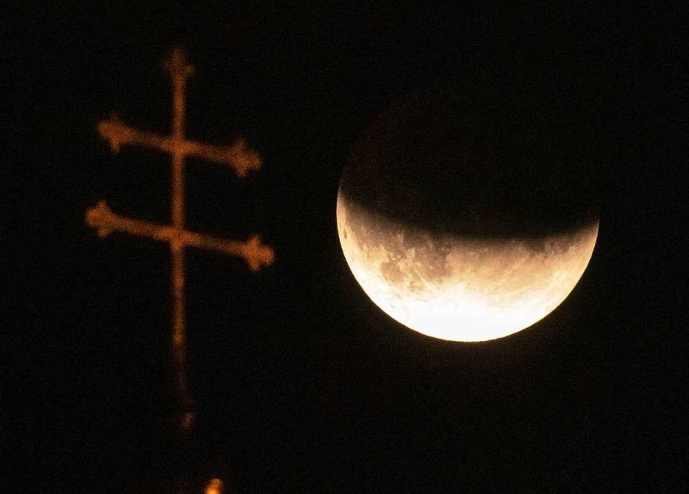 München:  Der Mond ist während einer p...m Dach der Heiliggeistkirche zu sehen.  | Foto: Peter Kneffel (dpa)