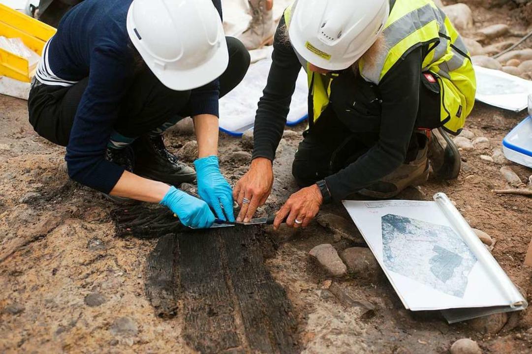 Bergung des verkohlten Fassdeckels, de...terlichen Holzgebäuden gefunden wurde.  | Foto: Adrian Jost (Achäologische Bodenforschung Basel-Stadt)