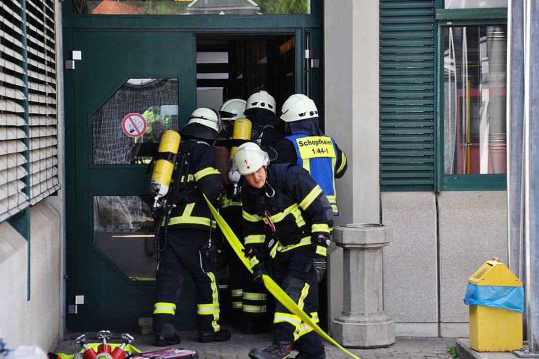 Feuerwehrleute rüsten sich mit Atemschutzgeräten für den Innenangriff.  | Foto: Nicolai Kapitz