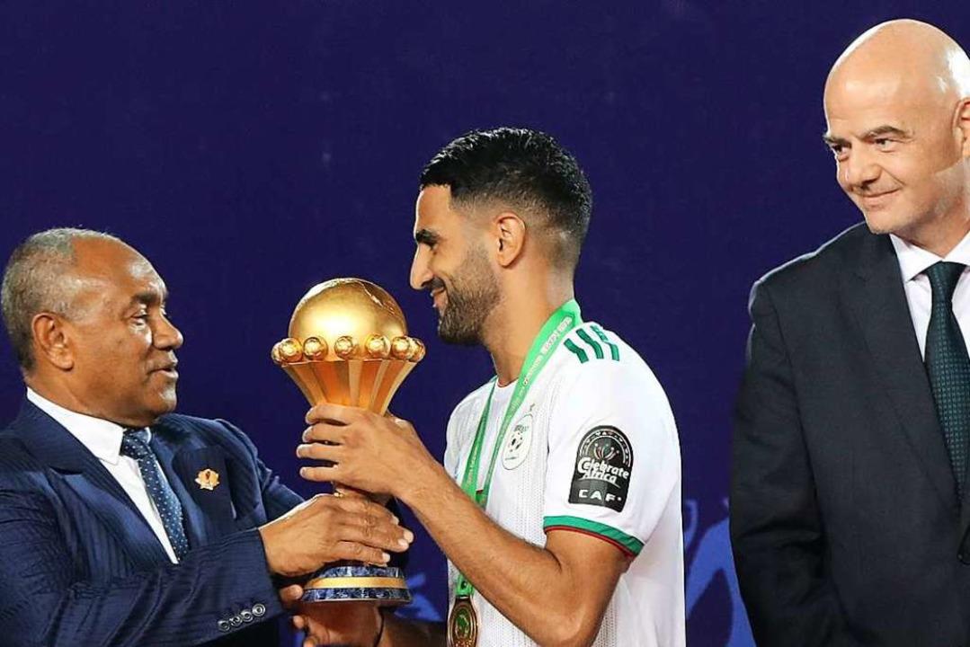 Der Siegtorschütze Riyad Mahrez (Mitte...t von FIFA-Präsident Gianni Infantino.  | Foto: Oliver Weiken (dpa)