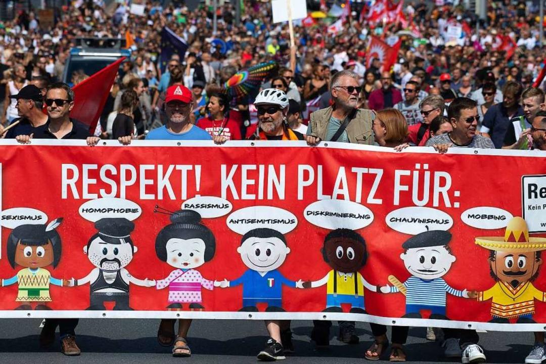 Teilnehmer einer Gegendemonstration ge... Plakaten und Flaggen durch die Stadt.  | Foto: Swen Pförtner (dpa)