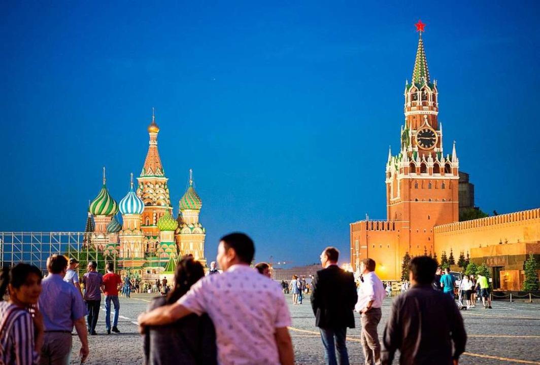 Besucher spazieren zur blauen Stunde auf dem Roten Platz.  | Foto: Christophe Gateau