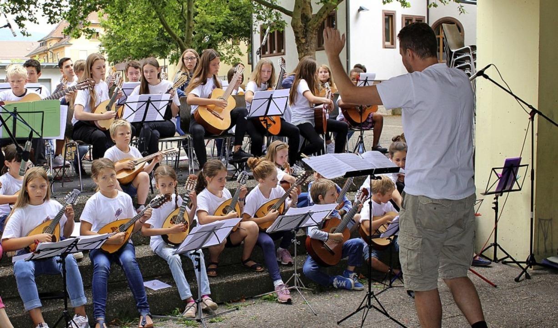 Das Jugendorchester sowie die Mandolin...spiel mit dem Dirigenten Jan Skryhan.   | Foto: Jana Fischer