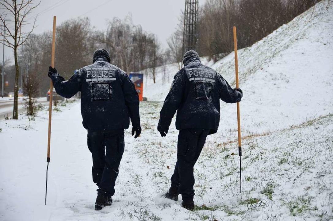 Im Dezember 2014 suchen Polizisten auf...elände rund um den Tatort nach Spuren.  | Foto: Julia Jacob