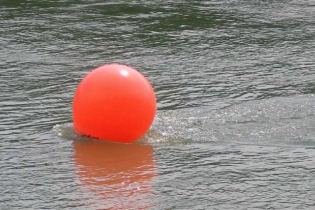 Schwimmer kann sich an Boje festhalten und wird von Badegästen gerettet