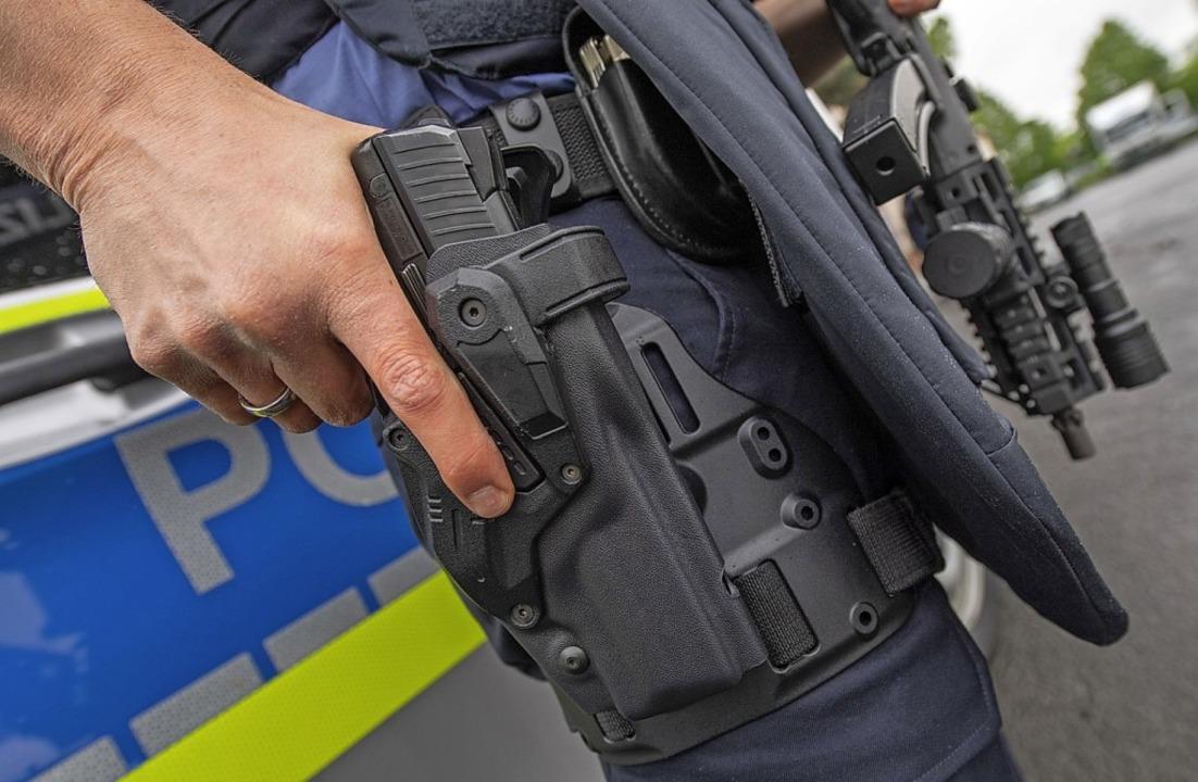 Der Polizist hat bei einer Übung seine Hand an der Pistole.  | Foto: Boris Roessler (dpa)