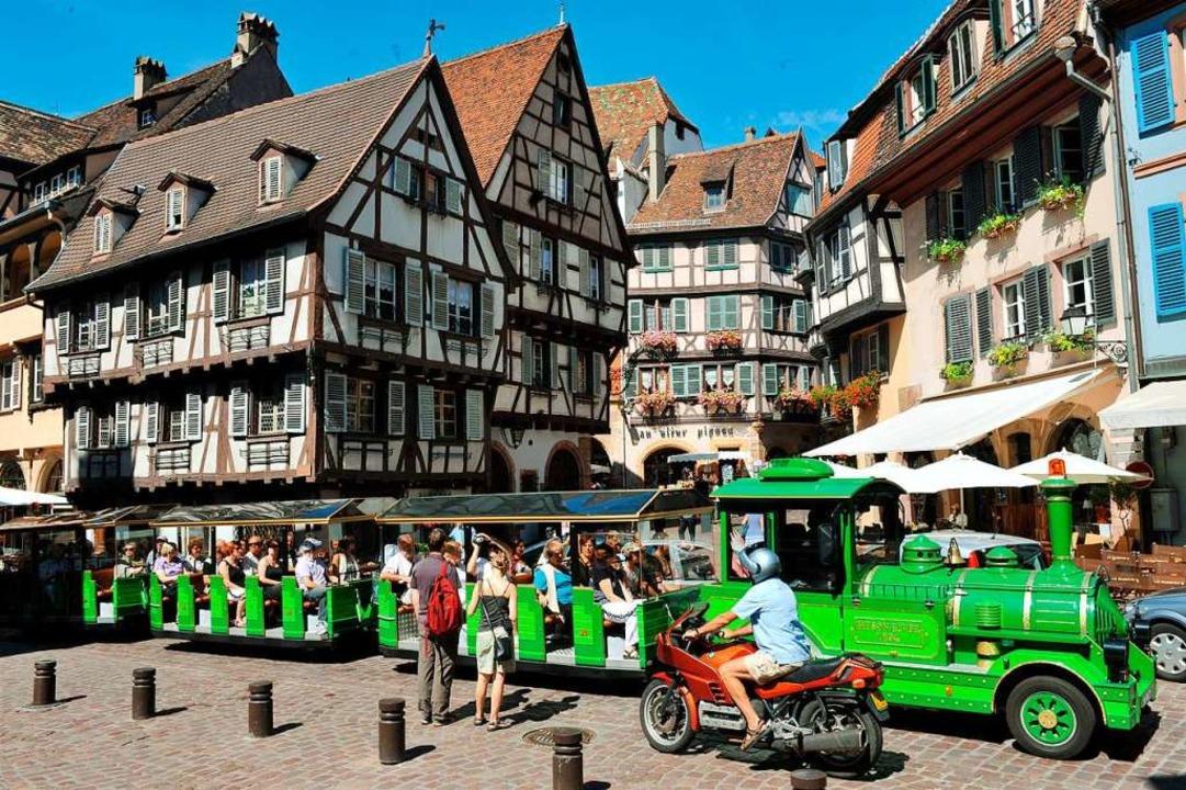 Touristen fahren mit einem Bähnchen du...s eigene Verwaltungseinheit auftreten.  | Foto: Rolf Haid