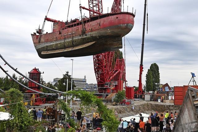 Kran hievt Schiff aus dem Rhein