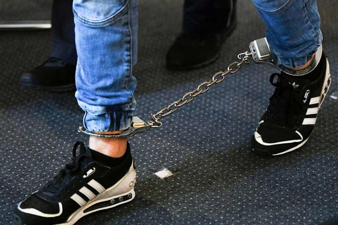 Ein Angeklagter wird am Freitag in Fuß...V des Freiburger Landgerichts geführt.  | Foto: Patrick Seeger (dpa)