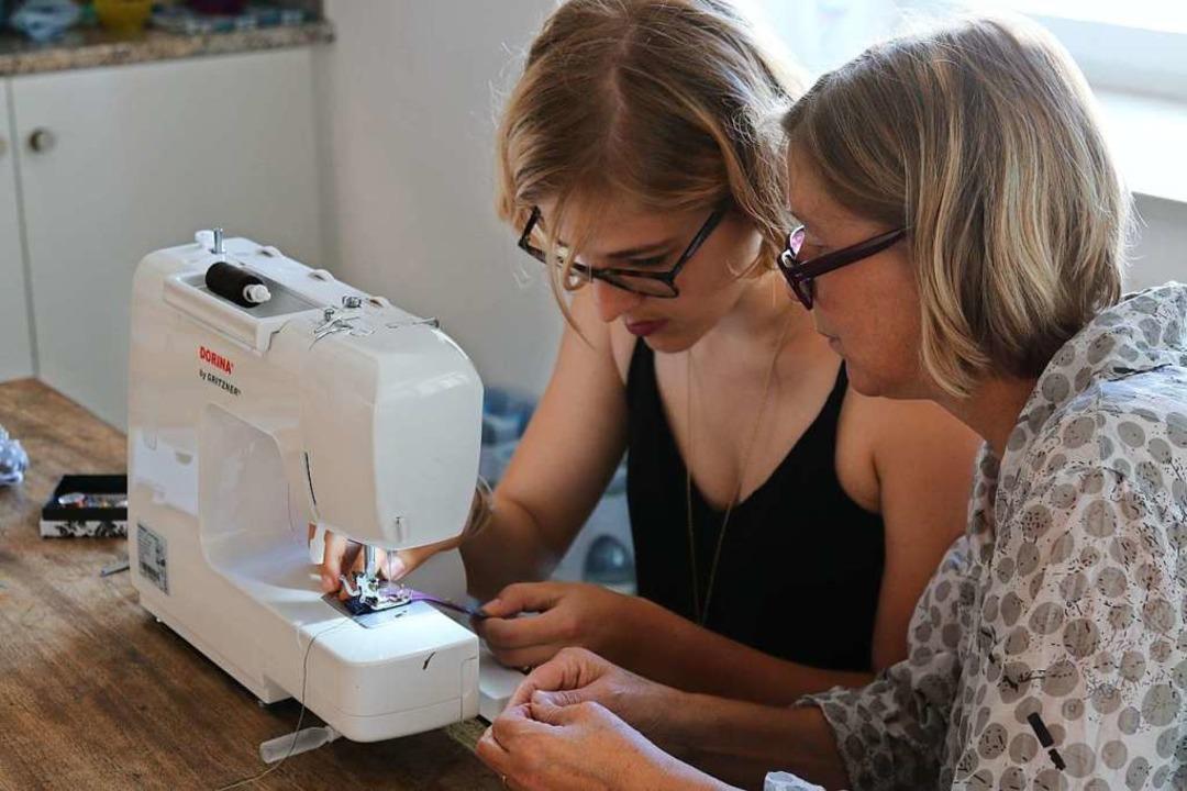 Heidi Pfeiffer (rechts) erklärt Nathal... einer Blusenknopfleiste ein Haarband.  | Foto: Katharina Kubon