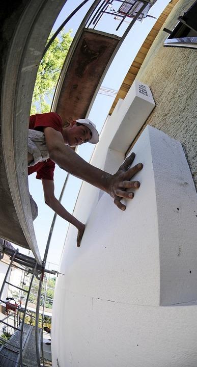 Ein Arbeiter dämmt ein Haus. Die Regie...ür die Gebäudesanierung bereitstellen.    Foto: Armin Weigel