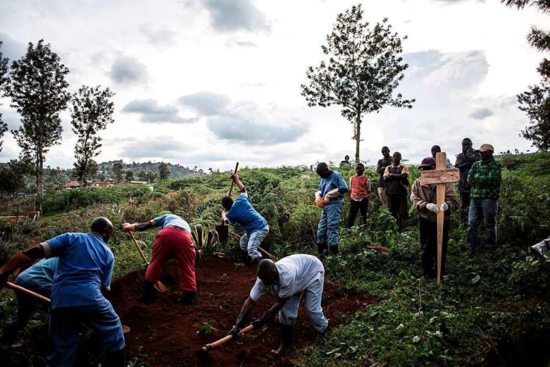 Eine Familie beerdigt in Butembo einen...sind mehr als 2600 Menschen infiziert.  | Foto: JOHN WESSELS (AFP)