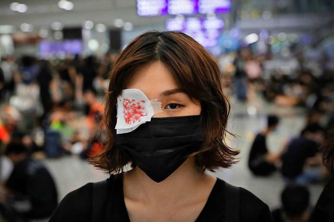 Eine Demonstrantin trägt auf dem Flugh...ergangenen Protesten zu protestieren.   | Foto: Kin Cheung (dpa)