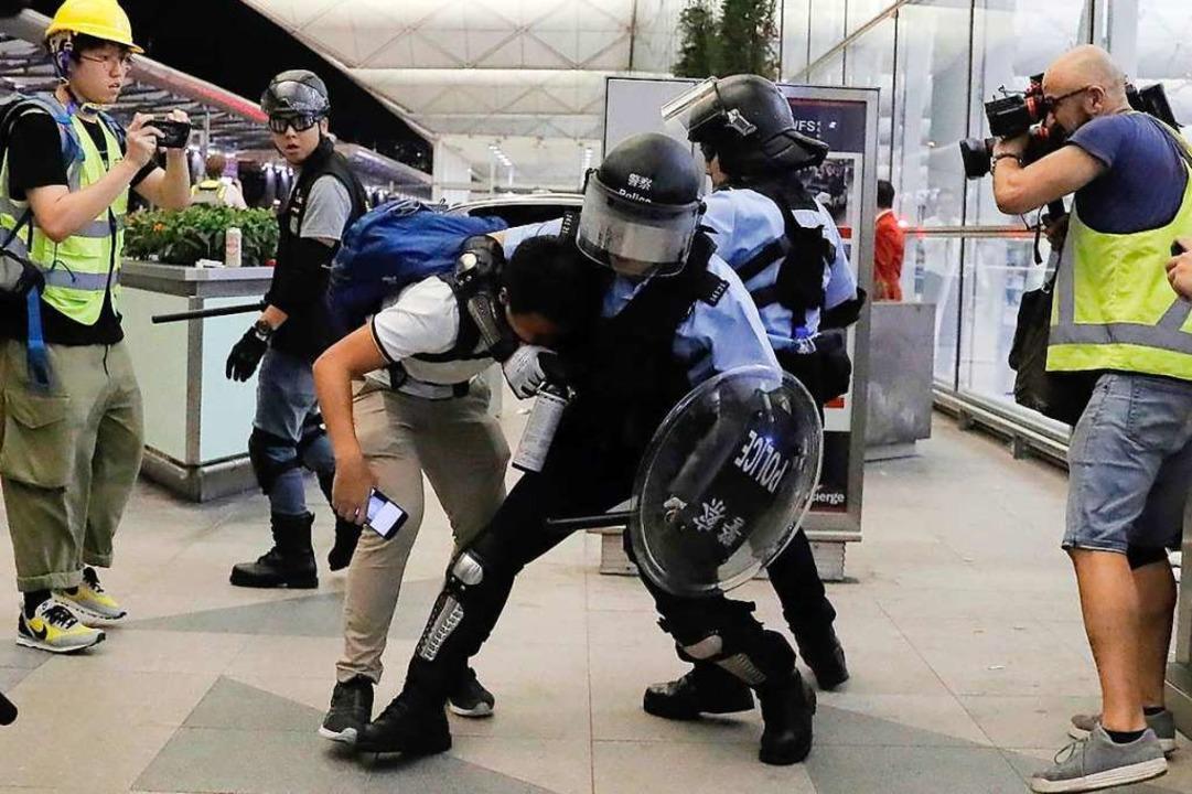 Polizisten gehen gegen Demonstranten in Hongkong vor.  | Foto: Kin Cheung (dpa)