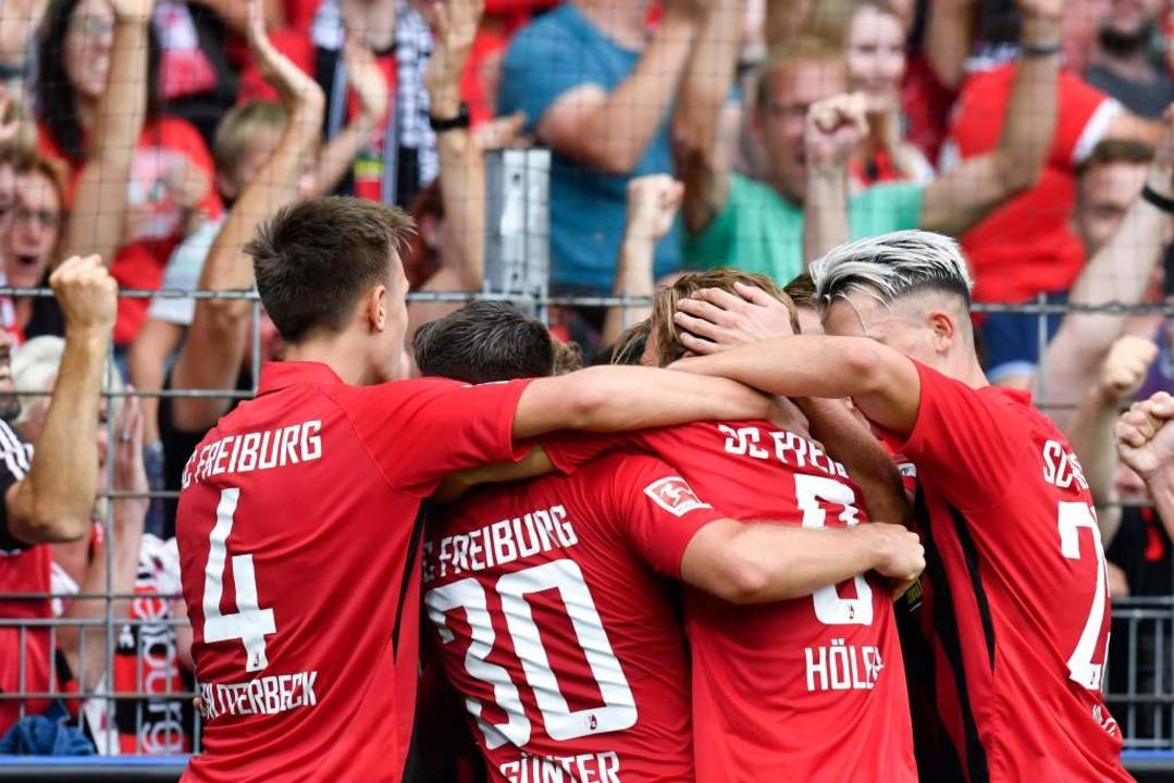 Die Freiburger jubeln vor den eigenen Fans.  | Foto: THOMAS KIENZLE (AFP)