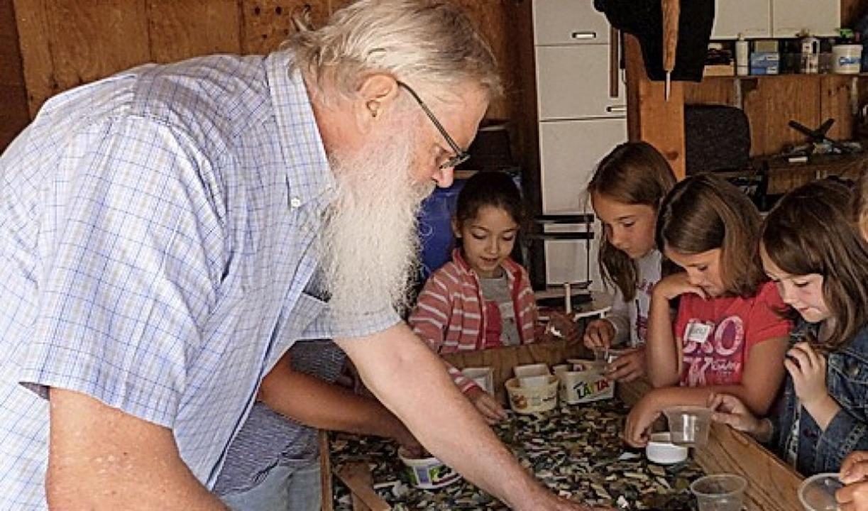 Künstler Wolfgang Fröse sucht beim Mos...den Kindern passende Glasscherben aus.  | Foto: suedkurier