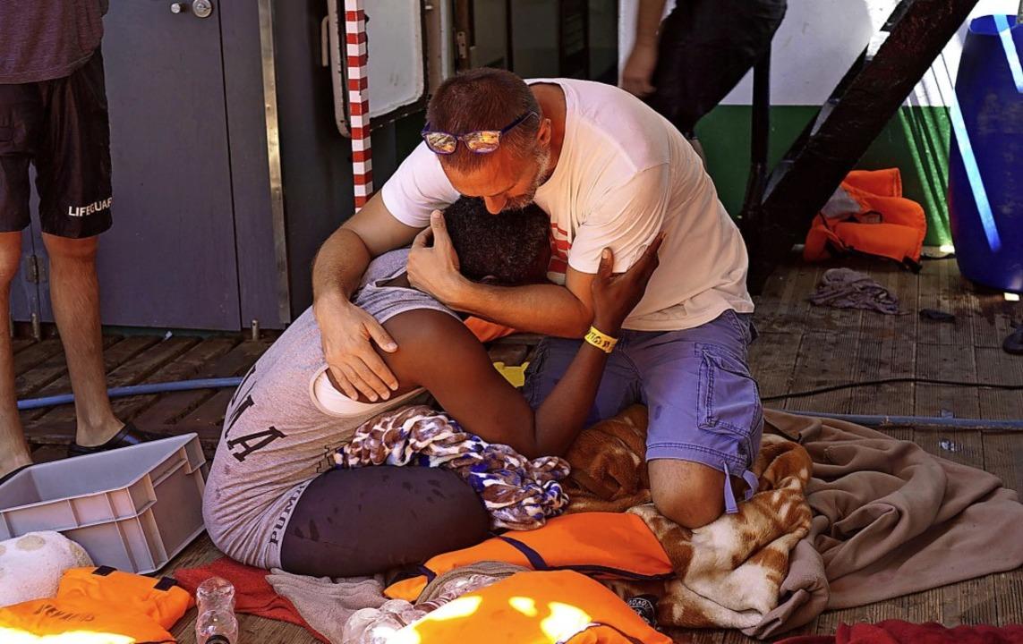 Ein Besatzungsmitglied des spanischen ...ms tröstet am Sonntag einen Migranten.    Foto: Francisco Gentico (dpa)
