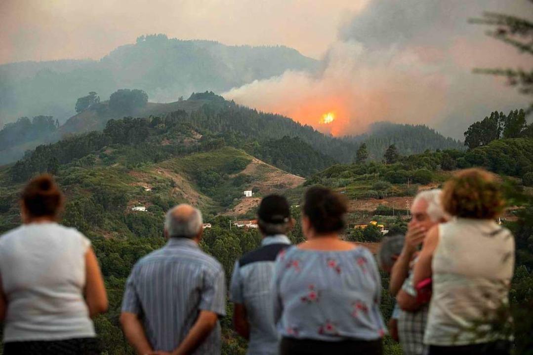 Anwohner schauen fassungslos auf die Brände.  | Foto: DESIREE MARTIN (AFP)