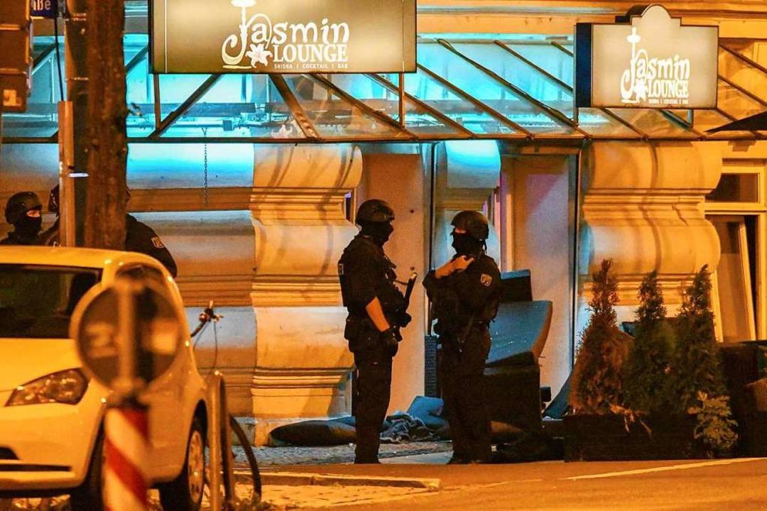 Polizisten in Schutzausrüstung stehen ...destens zwei Menschen verletzt worden.  | Foto: Tom Wunderlich (dpa)