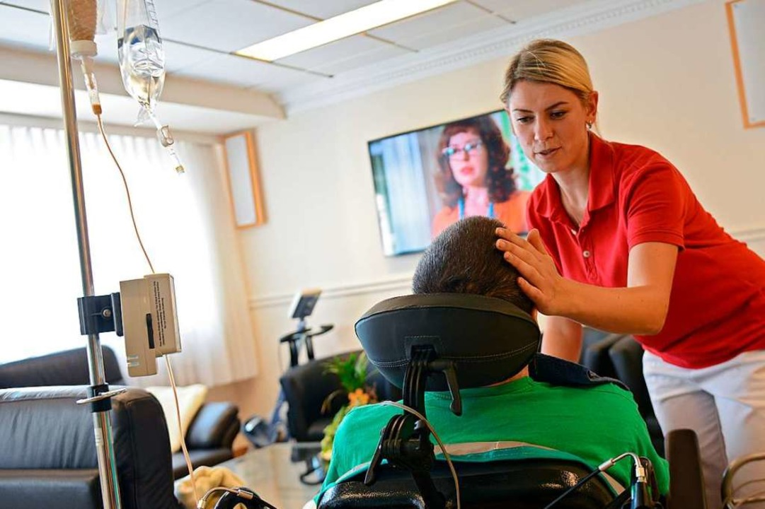 Eine Pflegerin kümmert sich um einen Patienten.  | Foto: Caroline Seidel