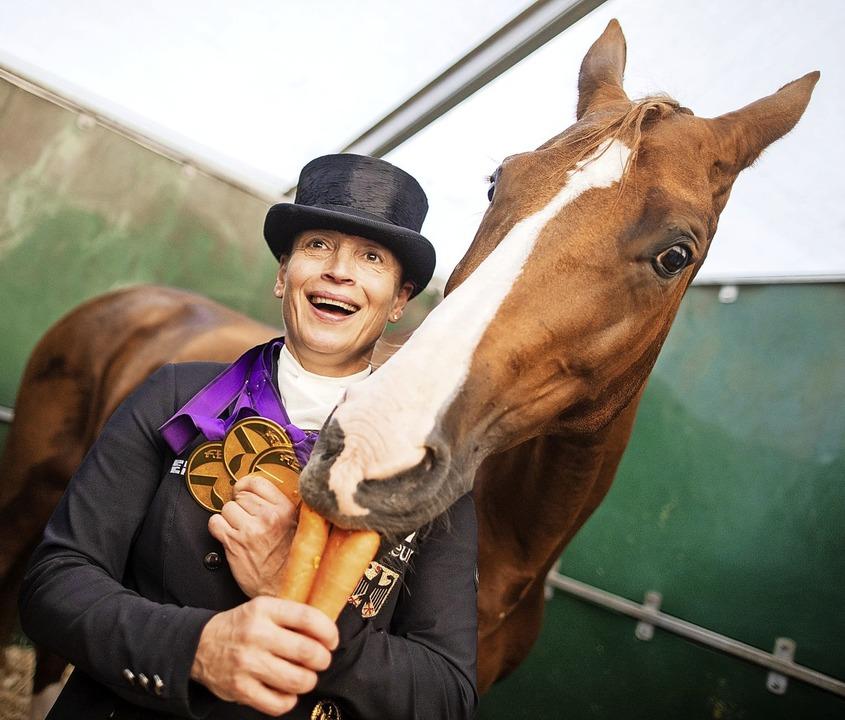 Dressurreiterin Isabell Werth feiert m...Pferd Bella Rose, das  Möhren erhält.   | Foto: Rolf Vennenbernd (dpa)