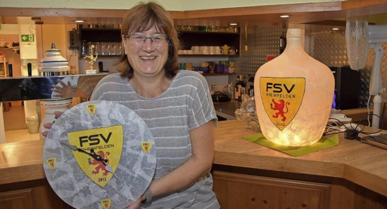 FSV-Wirtin Nicole Ranz mit ihrer selbs...tellten Vereinsuhr und Vereins-Lampe.   | Foto: Heinz und Monika Vollmar