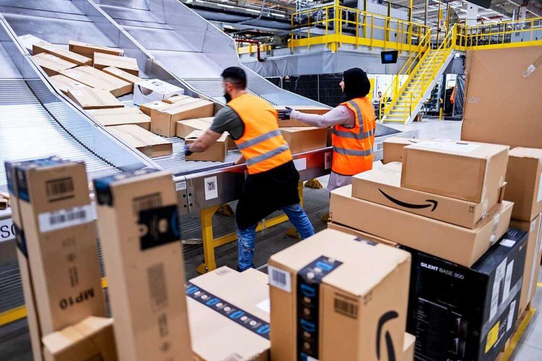 Mitarbeiter von Amazon sortieren Paket...tierzentrum in Garbsen, Niedersachsen.  | Foto: Peter Steffen (dpa)