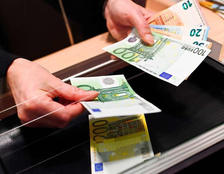 Ein Kunde zahlt Geld bei einer Bank ein.  | Foto: Angelika Warmuth